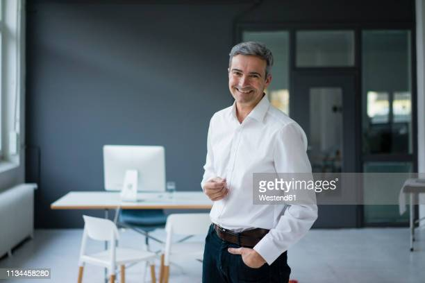 portrait of smiling businessman in the office - 襟付きシャツ ストックフォトと画像