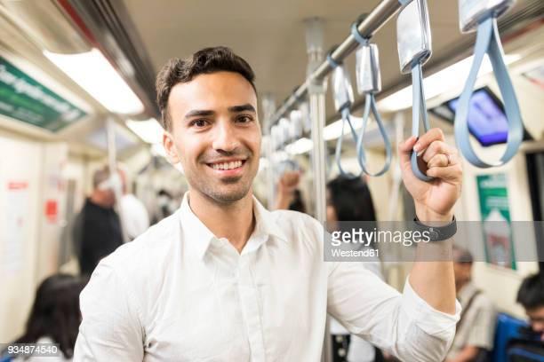 portrait of smiling businessman in the subway - transports publics photos et images de collection