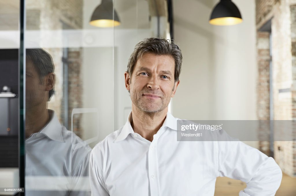 Portrait of smiling businessman leaning against glass pane : Stock Photo