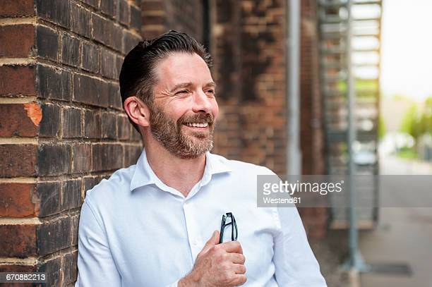 Portrait of smiling businessman leaning at brick wall