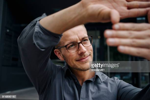 portrait of smiling businessman making finger frame - 身ぶり ストックフォトと画像
