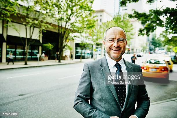 Portrait of smiling businessman on sidewalk