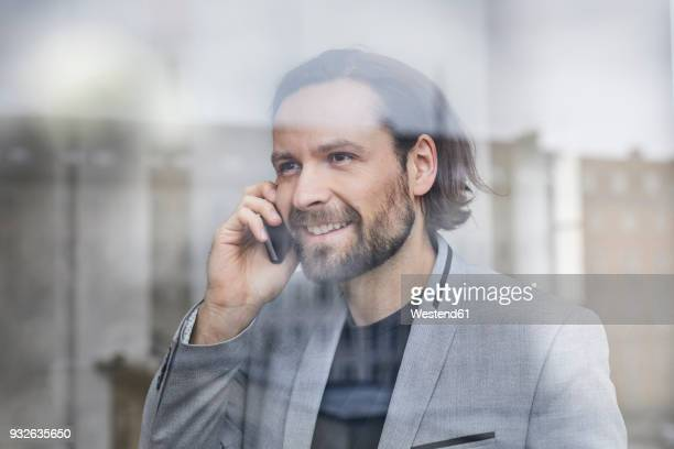 Portrait of smiling businessman on the phone behind windowpane
