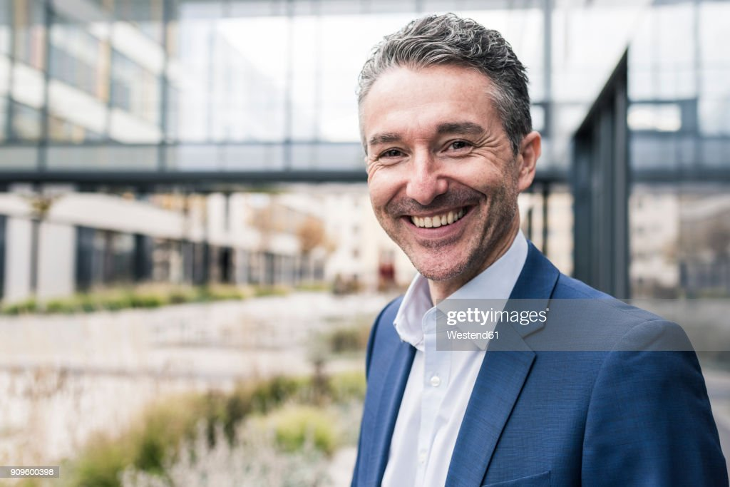 Portrait of smiling businessman outside office building : Stock-Foto