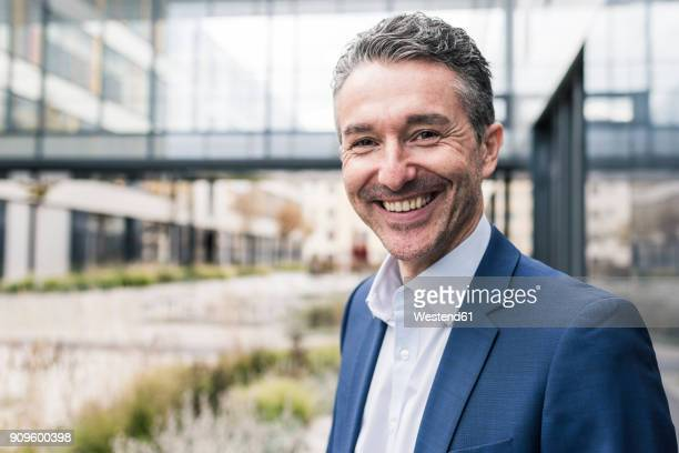portrait of smiling businessman outside office building - ein mann allein stock-fotos und bilder