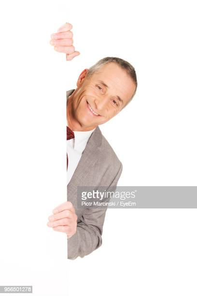 portrait of smiling businessman peeking from blank placard against white background - peeking stock pictures, royalty-free photos & images