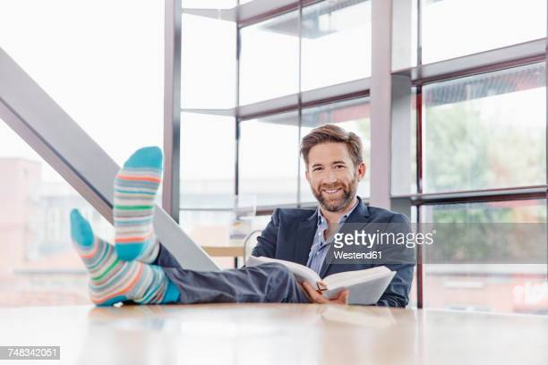 portrait of smiling businessman putting his feet on the table reading book - men wearing stockings stock photos and pictures