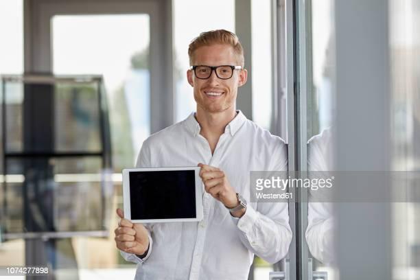 portrait of smiling businessman showing tablet at the window in office - tonen stockfoto's en -beelden