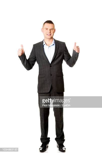 portrait of smiling businessman showing thumbs up while standing against white background - mid adult men fotografías e imágenes de stock