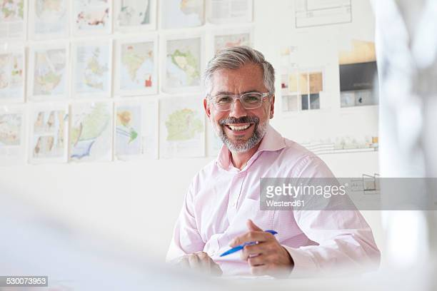 Portrait of smiling businessman sitting at his desk in an office