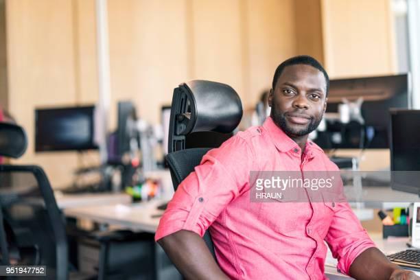 porträt von lächelnd geschäftsmann sitzt im büro - börsensaal stock-fotos und bilder
