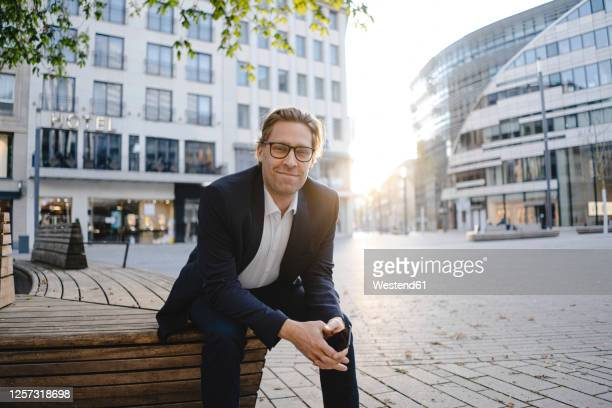 portrait of smiling businessman sitting on a bench in the city - sitzbank stock-fotos und bilder
