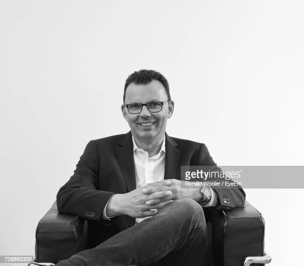 Portrait Of Smiling Businessman Sitting On Chair Against White Background