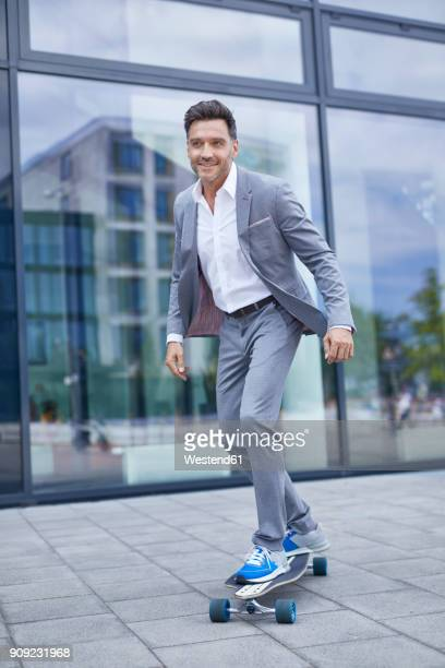 portrait of smiling businessman skateboarding on pavement - gray suit stock pictures, royalty-free photos & images