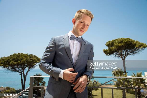 portrait of smiling businessman standing against sky - formal businesswear stock pictures, royalty-free photos & images