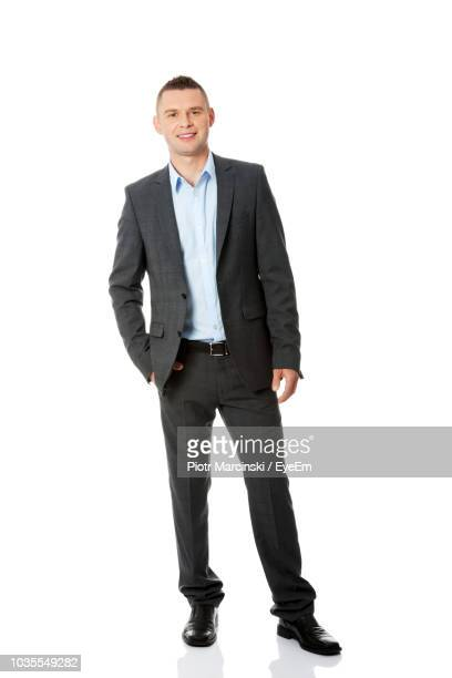 portrait of smiling businessman standing against white background - anzug stock-fotos und bilder