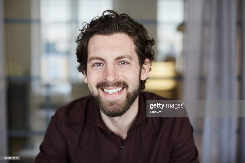Portrait of smiling businessman standing at creative office : Stock Photo