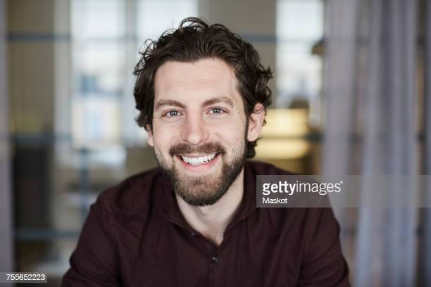 Portrait of smiling businessman standing at creative office