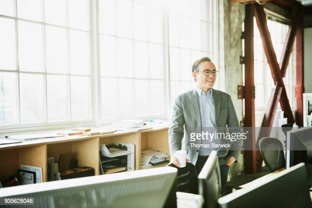 Portrait of smiling businessman standing at office workstation holding coffee cup