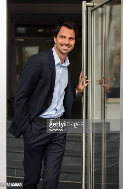 portrait of smiling businessman standing at open door - einzelner mann über 30 stock-fotos und bilder