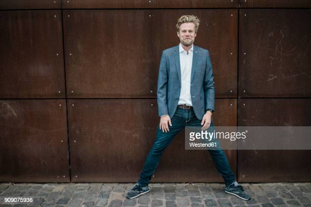 portrait of smiling businessman standing at rusty wall - benen gespreid stockfoto's en -beelden