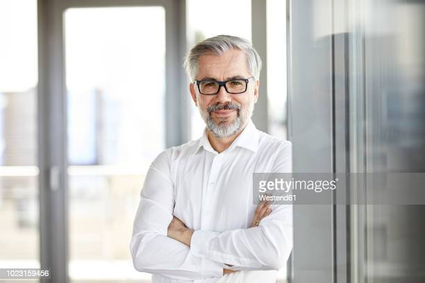 portrait of smiling businessman standing at the window - respekt stock-fotos und bilder