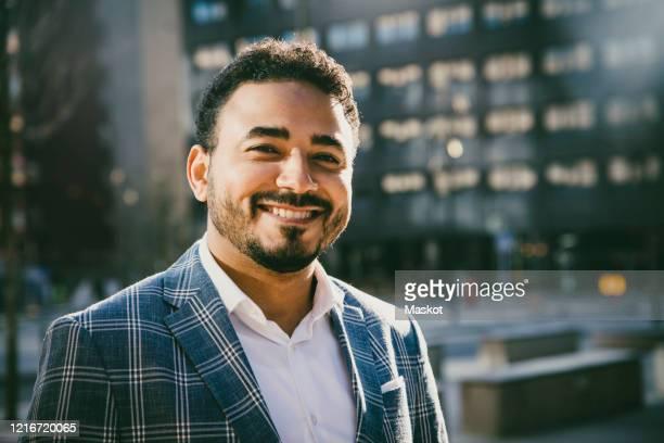 portrait of smiling businessman standing outside office building - mid adult men imagens e fotografias de stock