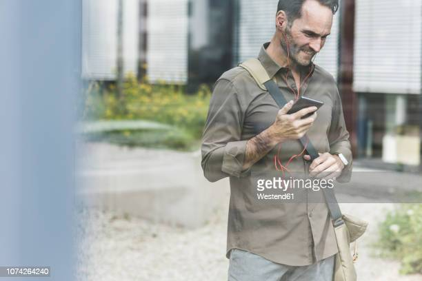 portrait of smiling businessman using smartphone and earphones - desaturated stock pictures, royalty-free photos & images