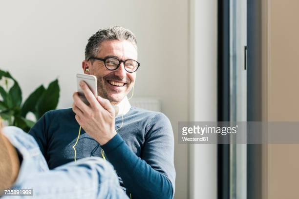 portrait of smiling businessman using smartphone and earphones - lässige kleidung stock-fotos und bilder