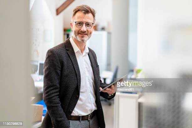 portrait of smiling businessman using tablet in office - formal businesswear stock pictures, royalty-free photos & images