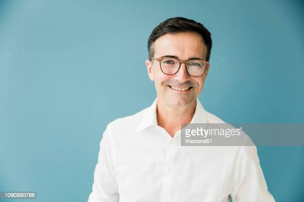 portrait of smiling businessman wearing glasses - sfondo a colori foto e immagini stock
