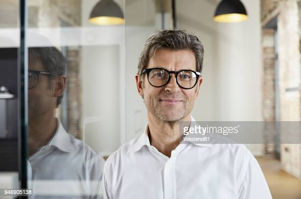 portrait of smiling businessman wearing glasses - männer über 40 stock-fotos und bilder
