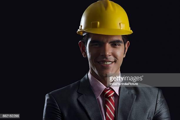 Portrait of smiling businessman wearing hardhat against black background