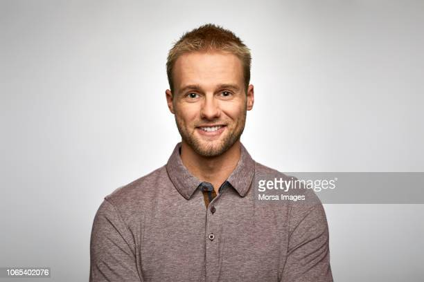 portrait of smiling businessman wearing t-shirt - mannen stockfoto's en -beelden