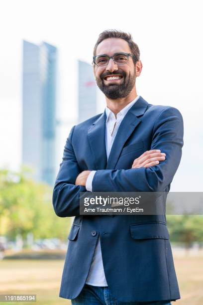 portrait of smiling businessman with arms crossed standing in park - mid adult men stock pictures, royalty-free photos & images