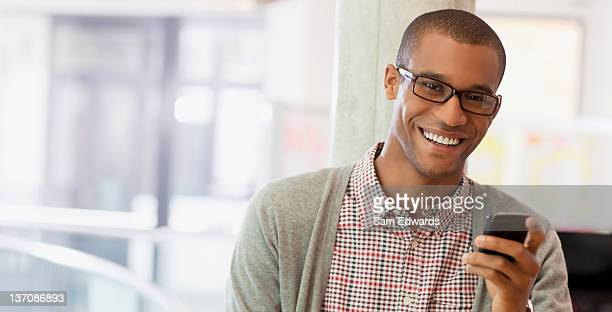 Portrait of smiling businessman with cell phone