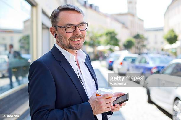 Portrait of smiling businessman with coffee to wearing earphones