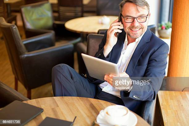 Portrait of smiling businessman with digital tablet sitting in a cafe telephoning with smartphone