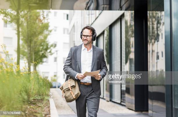 portrait of smiling businessman with documents and headphones - one mature man only stock pictures, royalty-free photos & images