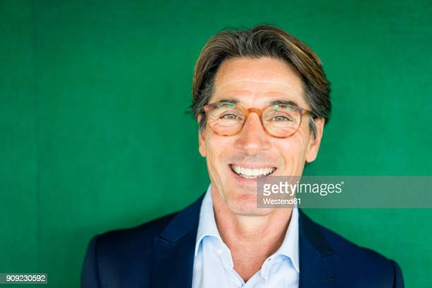 portrait of smiling businessman with glasses in front of green wall - grüner hintergrund stock-fotos und bilder