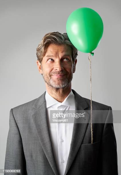 portrait of smiling businessman with green balloon - gründer stock-fotos und bilder