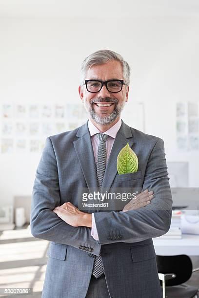 Portrait of smiling businessman with green leaf in his jacket pocket