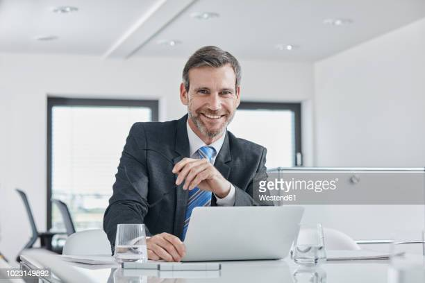 portrait of smiling businessman with laptop at desk in office - anzug stock-fotos und bilder