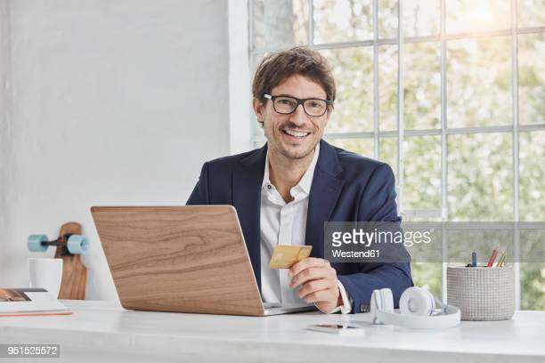 portrait of smiling businessman with laptop on desk holding credit card - charging sports stock pictures, royalty-free photos & images
