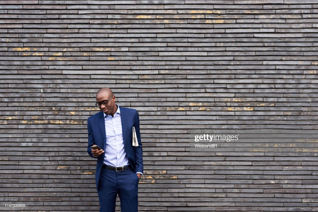 Portrait of smiling businessman with newspaper wearing glasses and blue suit looking at mobile phone : Foto stock