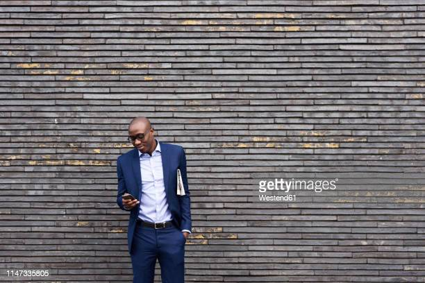 portrait of smiling businessman with newspaper wearing glasses and blue suit looking at mobile phone - zwart pak stockfoto's en -beelden