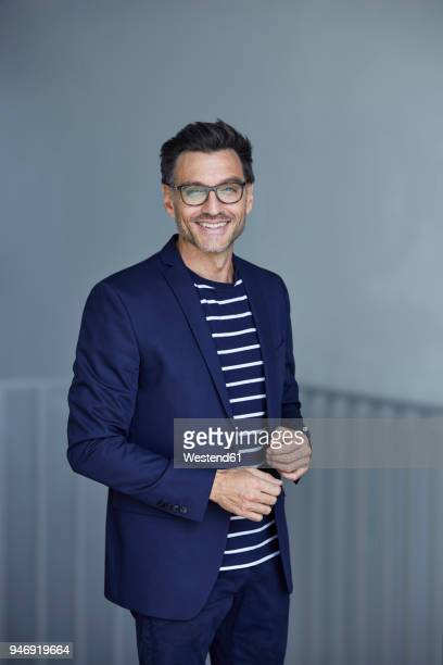 portrait of smiling businessman with stubble wearing blue suit and glasses - striped suit stock pictures, royalty-free photos & images