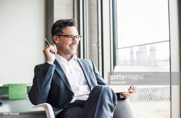 Portrait of smiling businessman with tablet looking through window