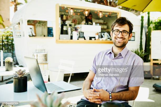 portrait of smiling businessman working on laptop at outdoor coffee shop - bracelet stock pictures, royalty-free photos & images