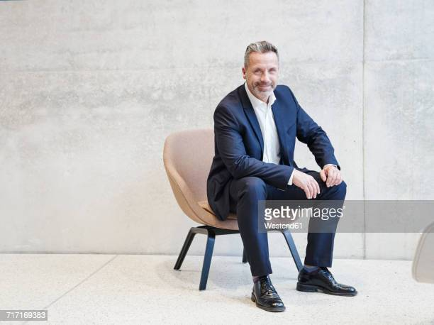 portrait of smiling businesssman sitting in armchair - sitzen stock-fotos und bilder
